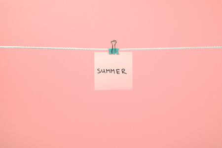 Pink paper note on clothesline with text Summer over colorful background