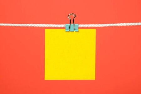 Blank yellow paper note on the string over color background Stock Photo