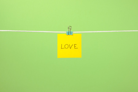 Yellow paper note on clothesline with text Love over colorful background