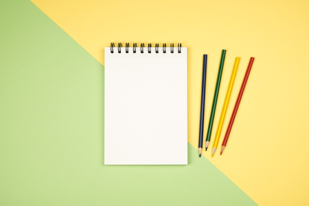 Top view of blank notebook page with colored pencils on table. Flat lay
