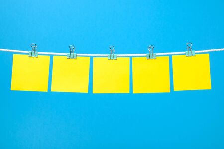 Blank yellow paper sheets on the string over color background Stock Photo