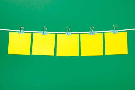 notepaper: Empty yellow paper notes on the string over color background Stock Photo