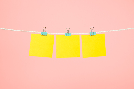 Blank yellow paper notes hanging on clothesline over pink background Stock Photo