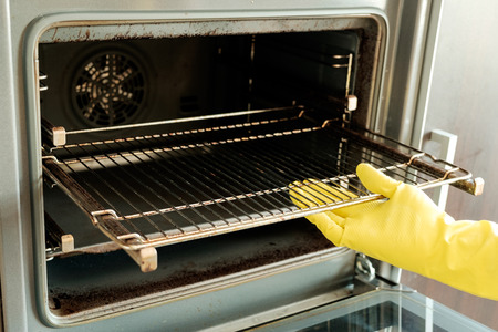 Close up of male hand with yellow protective gloves cleaning oven