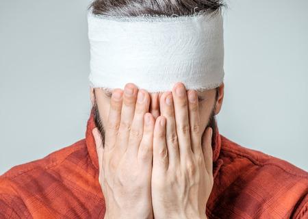 Retrato de hombre con vendas envueltas alrededor de su cabeza aislada en el fondo gris