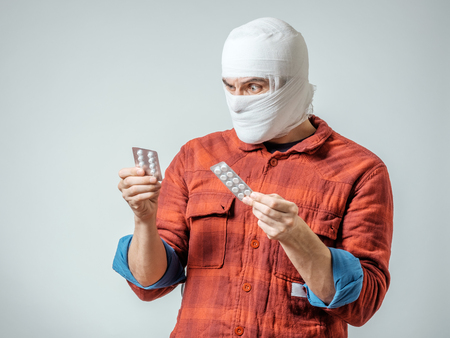 Sad injured bandaged man with pills over gray background