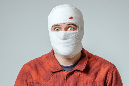 Close up portrait of injured man feeling the pain on his head isolated on gray background