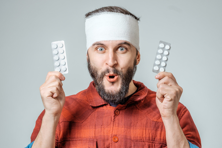 Man in medical bandage holding pills in a hand isolated on gray background Stock Photo