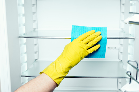 cleaning service: Mans hand in yellow gloves washing refrigerator inside with blue duster