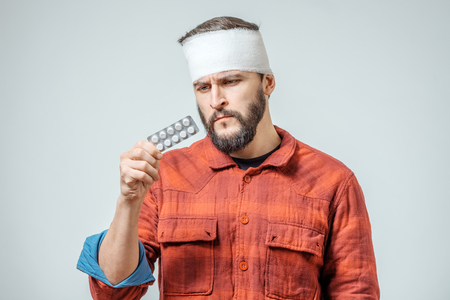 Sad injured bandaged man with pills over gray background