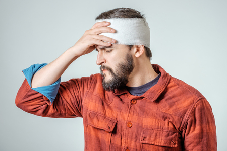 Portrait of man with bandages wrapped around his head isolated on gray background Banque d'images