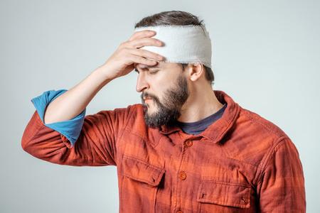 Portret van man met bandages om zijn hoofd gewikkeld geïsoleerd op grijze achtergrond