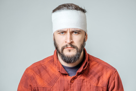 Portrait of man with bandages wrapped around his head isolated on gray background Stock Photo