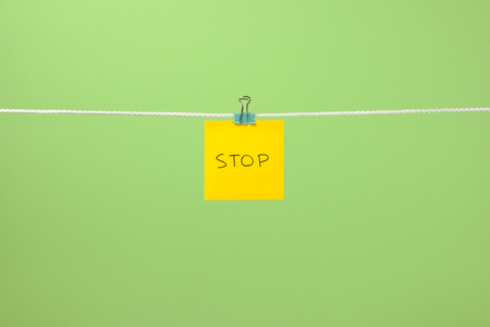 Yellow paper sheet on the string with text Stop over colorful background