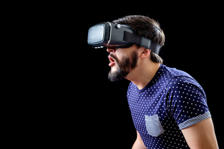 Portrait of bearded male with virtual reality glasses on his head isolated on black background Stock Photo