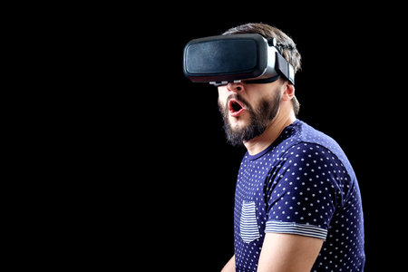 Young happy man experiencing virtual reality through a VR headset isolated on black