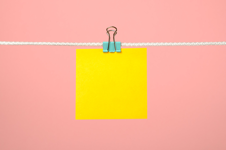 Blank yellow paper note on the string over pink background