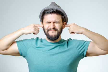 plugging: Annoyed young man plugging ears with hands isolated Stock Photo