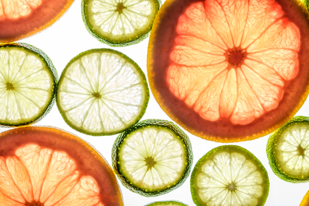Bright lime and grapefruit slices. Juicy transparent fruit on white