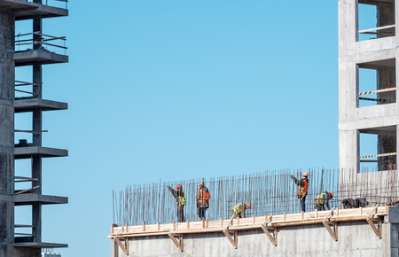 worker working: Construction. Urban landscape. Blue sky. Building Stock Photo