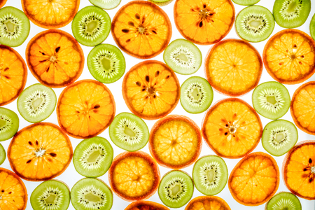 Mandarin and kiwi slices in different colors on white background