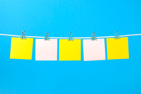 Blank yellow and pink paper notes on the string over color background