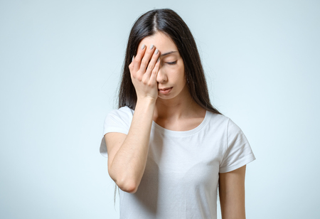 Portrait of depressed woman touching her head isolated over gray background