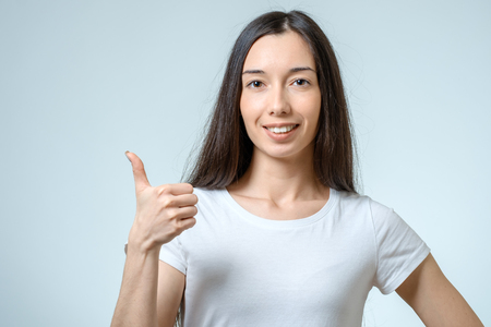Smiling happy young brunette woman showing thumbs up gesture isolated on white background Stock Photo
