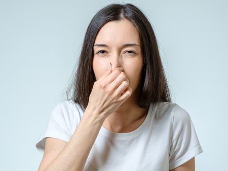 Girl covers nose with hand showing that something stinks isolated on gray background 스톡 콘텐츠