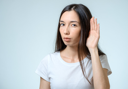 rumour: Beautiful young woman listening gossips and holding her hand near the ear isolated on white Stock Photo