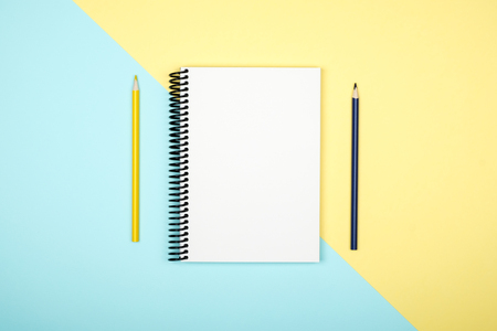 Top view of open spiral blank notebook on colorful desk background