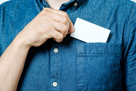 Mans hand takes out blank business card from the pocket of blue shirt