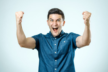 灰色の背景の彼の手を上げる幸せな若い男の肖像