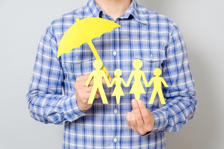 insurer: Man holding model of family and umbrella. Concept of family insurance with umbrella protecting a family
