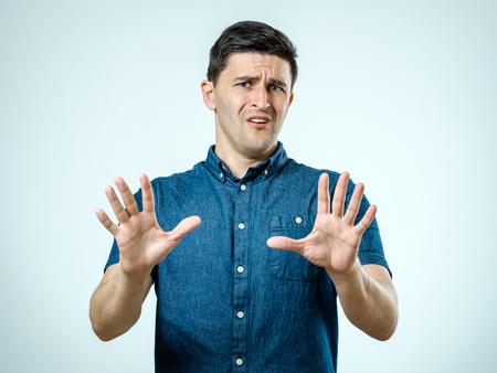 Mann mit erschrockenem Ausdruck auf seinem Gesicht, das erschrockene Geste mit seinen Palmen macht, als ob, versuchend, sich von jemand zu verteidigen