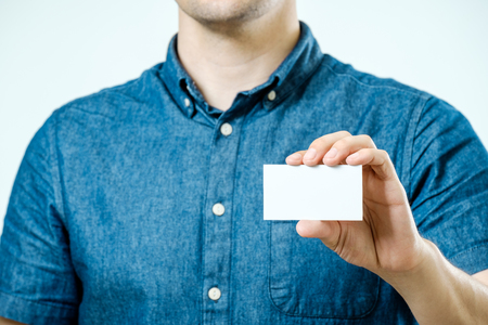 Man showing white blank business card on isolated background. Focus on card