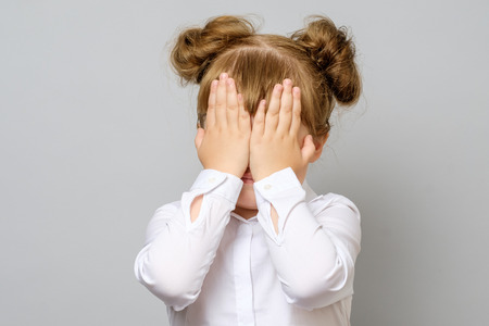 Girl covering her eyes with her hands isolated Stock Photo
