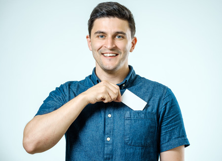 Young man who takes out blank business card from pocket of shirt. Isolated background
