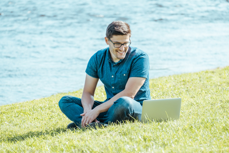 Young man with laptop outdoor sitting on the grass. Remote working concept