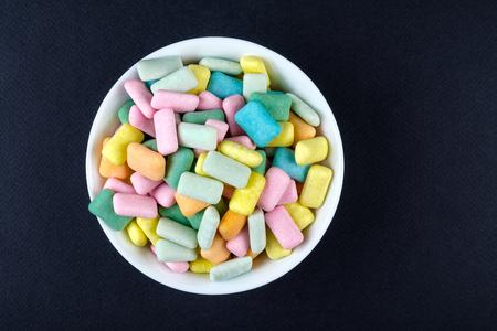 Chicle de colores en un tazón blanco Foto de archivo - 87527932