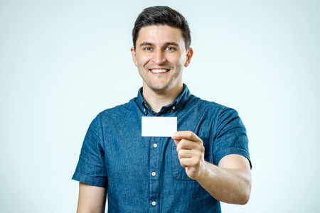 Young man showing blank business card or sign. Isolated on gray