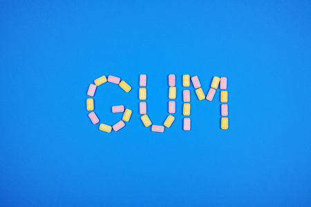 Word GUM written with chewing gum on blue background Stockfoto