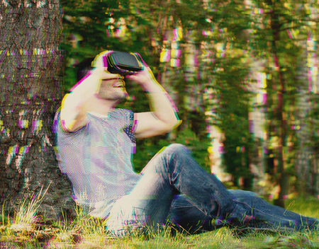 Man with VR goggles exploring virtual reality. Digital glitch effects added Stock Photo