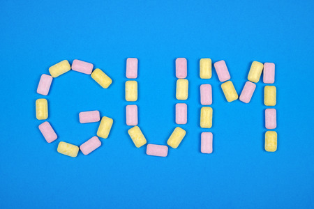 Word GUM written with chewing gum on blue background Stock Photo