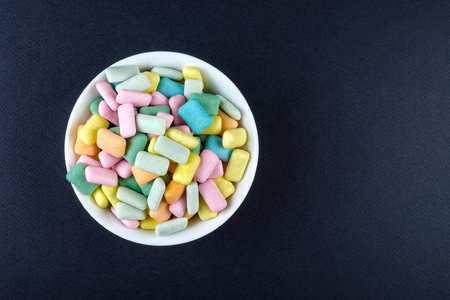 Colored chewing gum in a white bowl