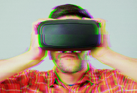 Man with VR goggles exploring virtual reality. Digital glitch effects added Stockfoto