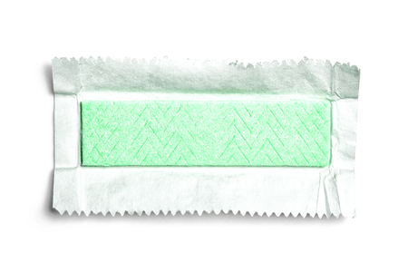 Top view of green unwrapped chewing gum on white background with paper or foil