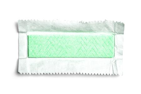 Bovenaanzicht van groene onverpakte kauwgom op witte achtergrond met papier of folie