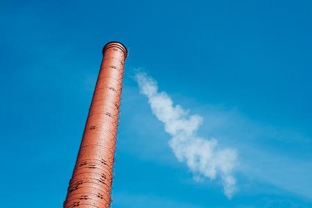 Red brick chimney with smoke on blue sky background
