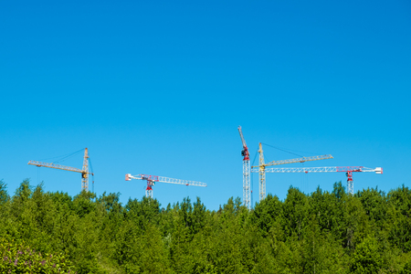 Side with cranes against blue sky. High building under construction Stock Photo